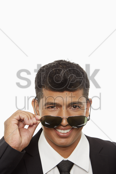 businessman pulling down his sunglasses stock photo