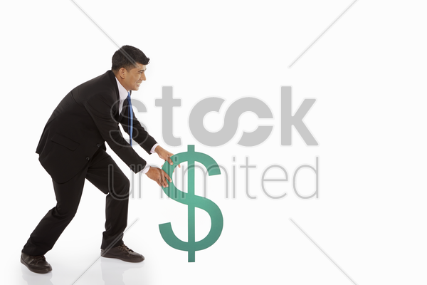businessman pulling the dollar sign stock photo