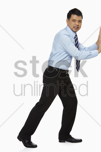 businessman pushing a wall stock photo