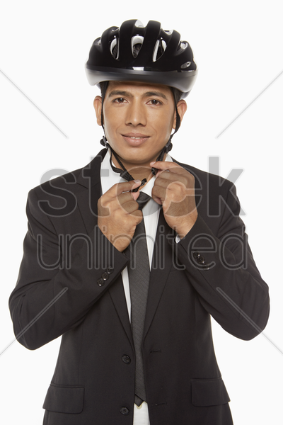 businessman putting on a bicycle helmet stock photo