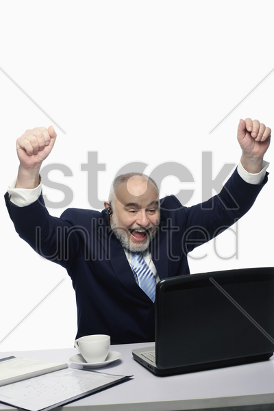 businessman raising his arms while using laptop stock photo