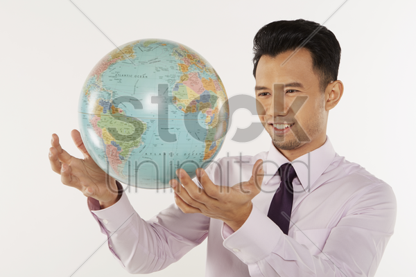 businessman reaching out for the globe stock photo