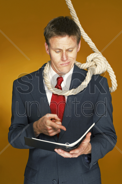 businessman reading a document with a rope hanging around his neck stock photo