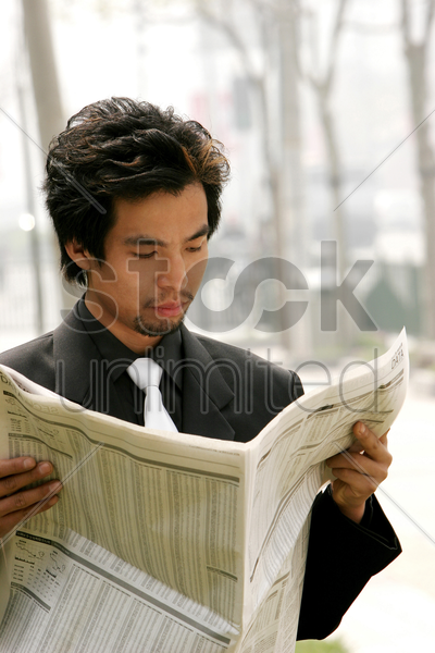 businessman reading newspaper by the roadside stock photo