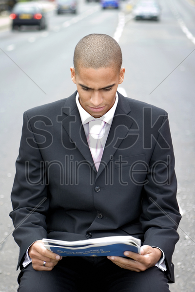 businessman reading newspaper in the middle of the road stock photo