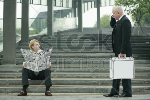 businessman reading newspaper on the stairs, another businessman carrying briefcase stock photo
