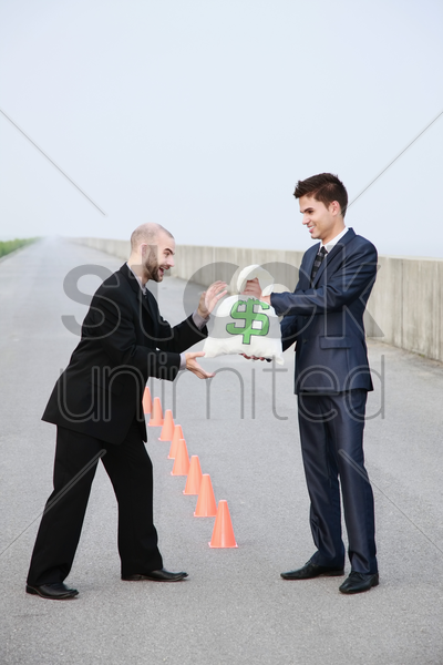 businessman receiving a bag of money from another businessman stock photo