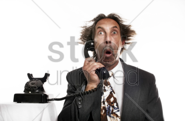 businessman receiving a shocking phone call stock photo