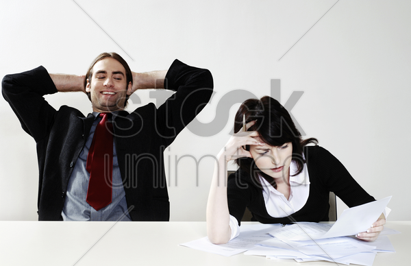 businessman relaxing while his colleague is busy with her work stock photo