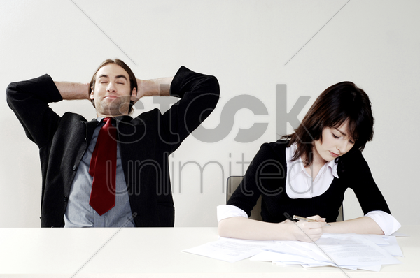 businessman relaxing while his colleague is doing her work stock photo
