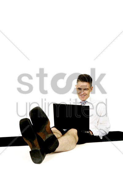 businessman resting his legs on the table while using laptop stock photo