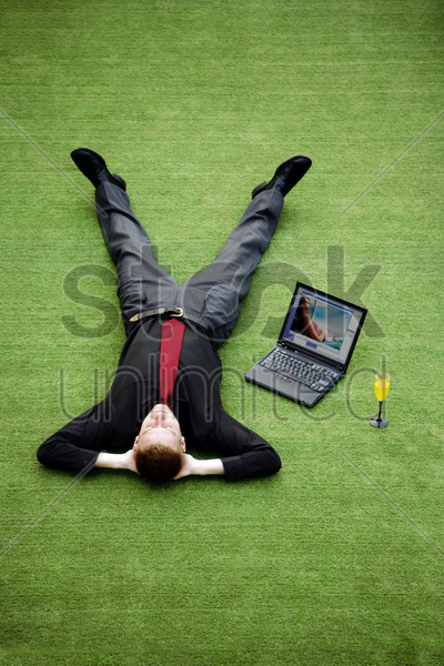 businessman resting on the field with his laptop by the side stock photo