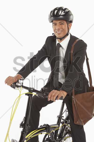 businessman riding a bicycle stock photo