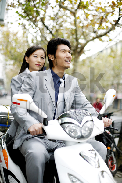 businessman riding on a scooter with businesswoman sitting behind him stock photo