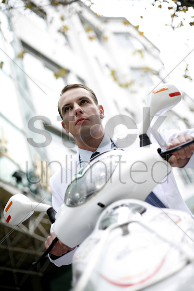businessman riding on a scooter stock photo