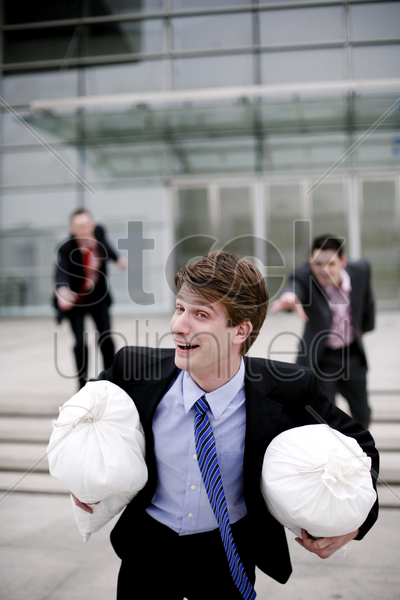 businessman running after stealing two bags of money stock photo
