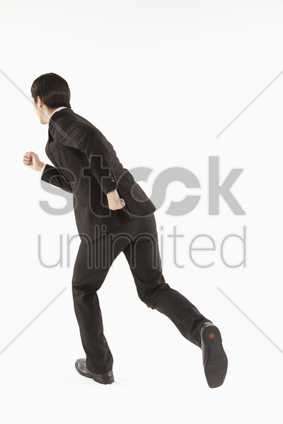businessman running, back facing camera stock photo