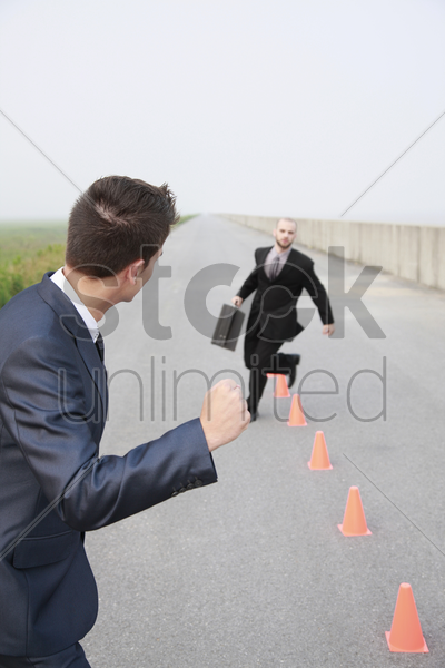 businessman running in between traffic cones, another businessman cheering stock photo