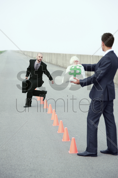 businessman running in between traffic cones, another businessman holding a bag of money stock photo