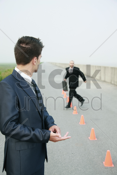 businessman running in between traffic cones, another businessman watching stock photo