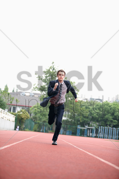 businessman running on track stock photo