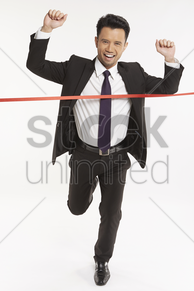 businessman running towards the finishing line stock photo