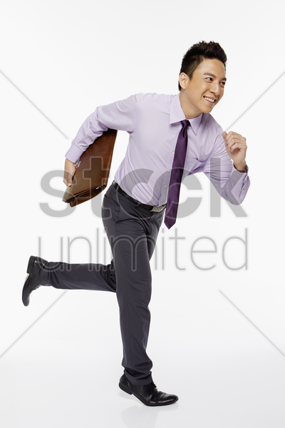 businessman running while carrying briefcase stock photo