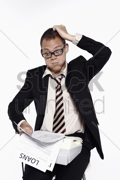 businessman scratching head while looking at his bills stock photo