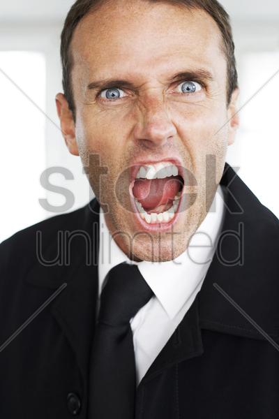 businessman screaming at the camera stock photo