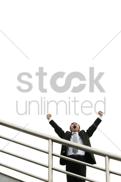 businessman screaming while raising his hands stock photo