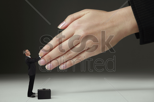 businessman shaking hands with giant sized hands stock photo