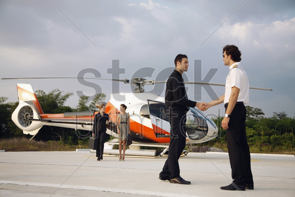 businessman shaking hands with pilot, businesswomen are walking from helicopter in the background stock photo