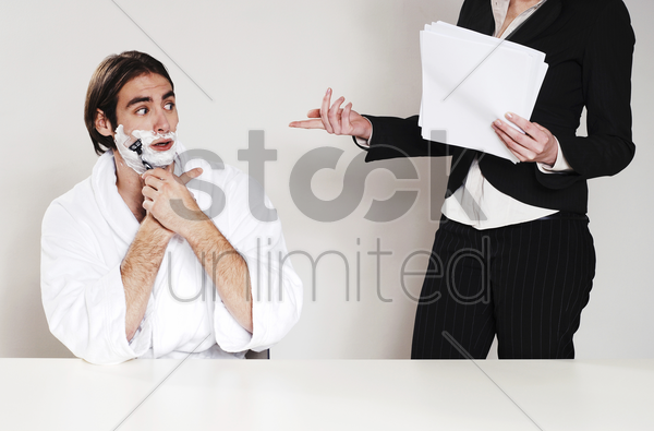 businessman shaving his beard in the office stock photo