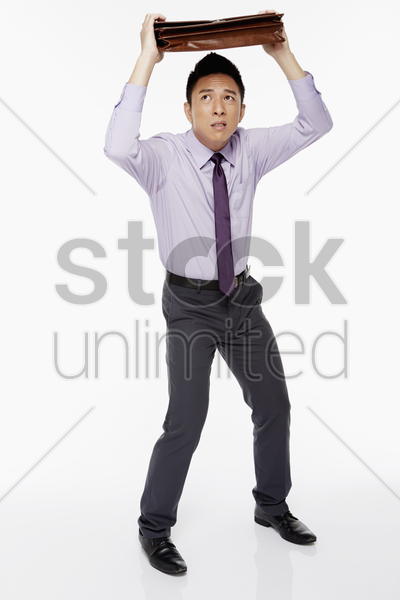 businessman shielding his head with a briefcase stock photo