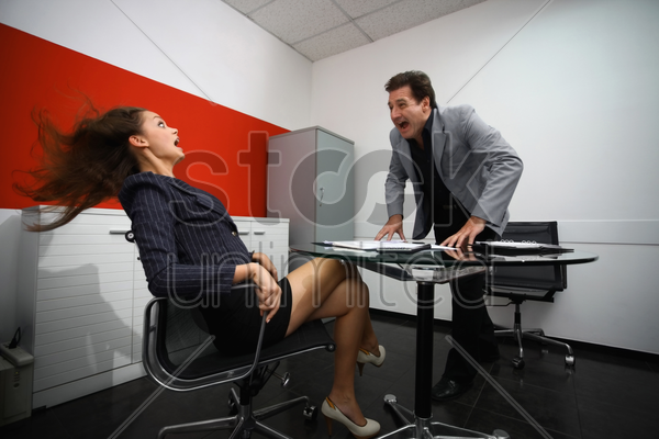 businessman shouting at businesswoman stock photo