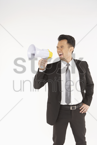 businessman shouting into a megaphone stock photo
