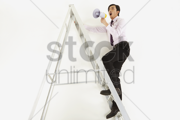 businessman shouting into megaphone stock photo