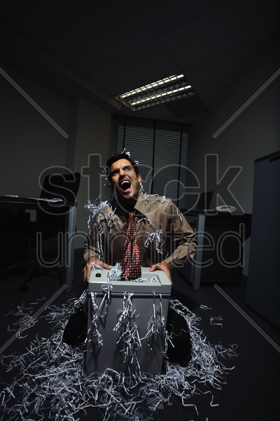 businessman shouting whiles his tie getting caught in a paper shredder stock photo