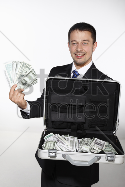 businessman showing a briefcase of money stock photo