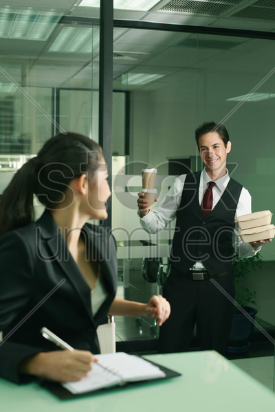 businessman showing businesswoman the take-out lunch that he bought stock photo