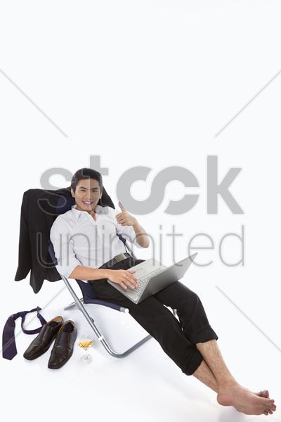 businessman showing hand gesture while using laptop stock photo