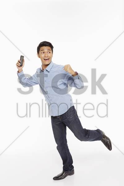 businessman showing hand gesture while using mobile phone stock photo