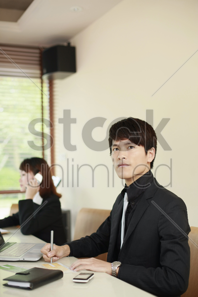 businessman signing cheque, businesswoman talking on the phone in the background stock photo