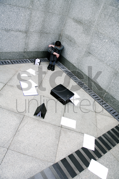 businessman sitting at the corner of a building stock photo