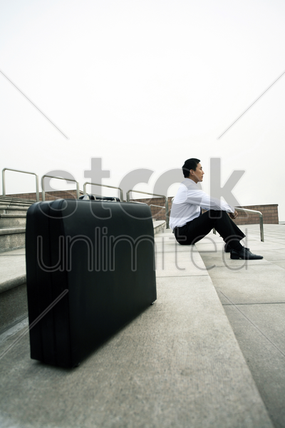 businessman sitting at the staircase with the focus on the briefcase stock photo