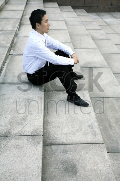 businessman sitting at the staircase stock photo