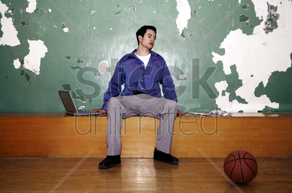 businessman sitting in a basketball court stock photo