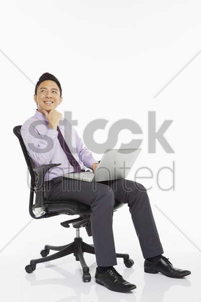 businessman sitting on a chair and using laptop stock photo