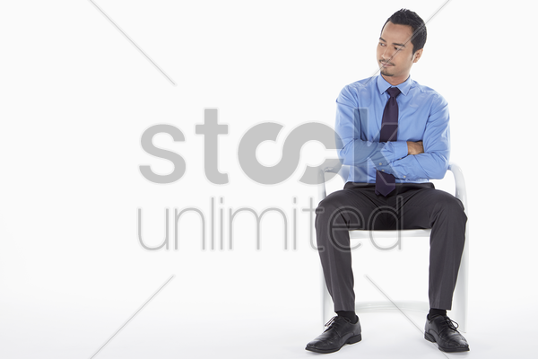 businessman sitting on a chair, facing right stock photo
