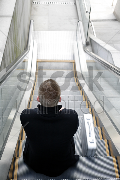businessman sitting on a moving escalator stock photo
